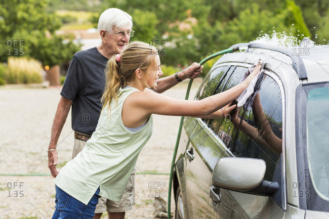 Senior man, grandfather and his 13 year old grand daughter washing a car together in driveway