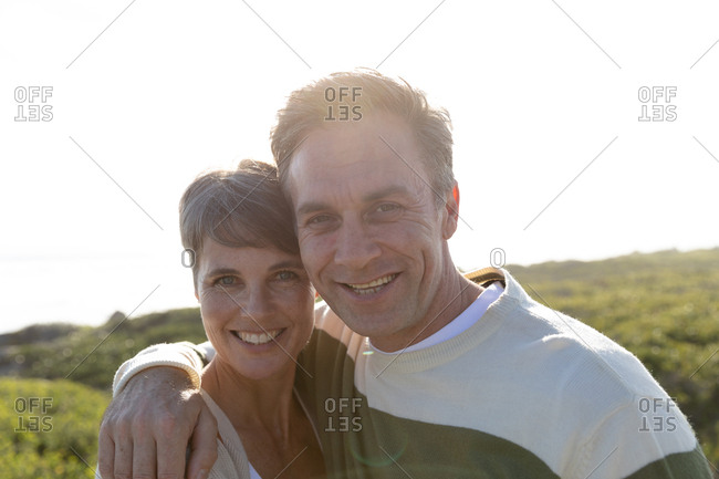 Portrait of an happy peaceful adult middle aged Caucasian couple enjoying free time smiling at the camera on a sunny day.