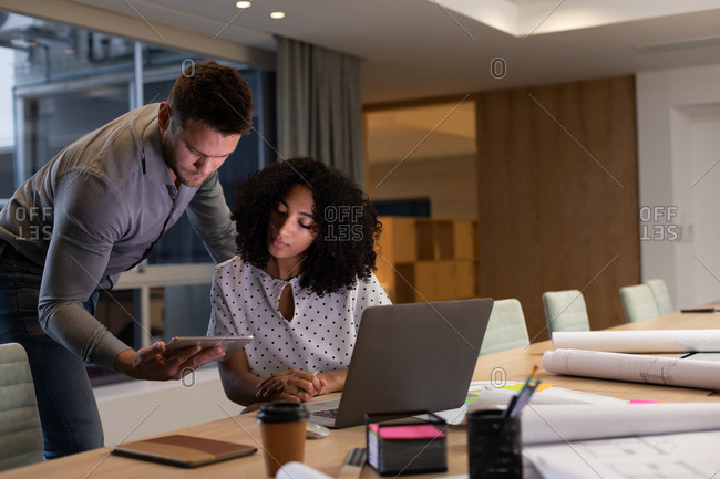 Front view of a young Caucasian professional man and mixed race woman working late in a modern office at a desk, using a laptop computer and looking at a tablet together