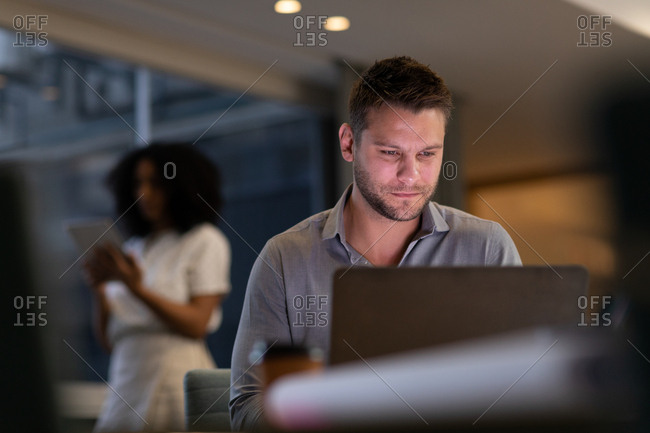Front view close up of a young Caucasian professional man and mixed race woman working late in a modern office, the man sitting at a desk using a laptop computer and the woman standing in the background using a tablet