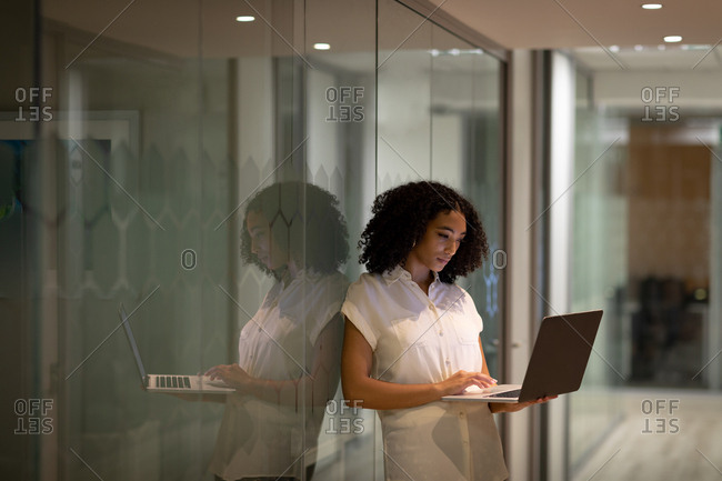 Front view of a young mixed race professional woman working late in a modern office, standing in the corridor using a laptop computer, reflected in a glass wall