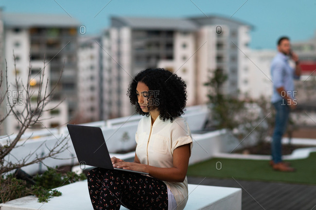 Front view of a young mixed race professional woman working late at a modern office, sitting on the roof terrace using a laptop computer, her male colleague standing in the background