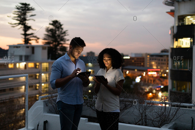 Front view of a young Caucasian professional man and mixed race woman working late at a modern office, standing on the roof terrace using tablet computers