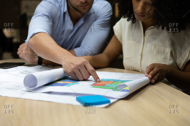 Front view close up of a young Caucasian professional man and mixed race woman working late in a modern office, sitting at a desk looking at plans together