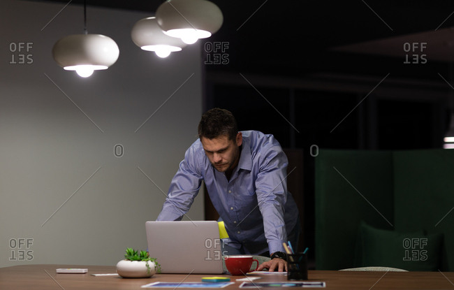 Front view of a young Caucasian professional man working late in a modern office, standing at a desk using a laptop computer