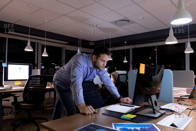 Front view of a young Caucasian professional man working late in a modern office, standing at a desk staring at a desktop computer monitor