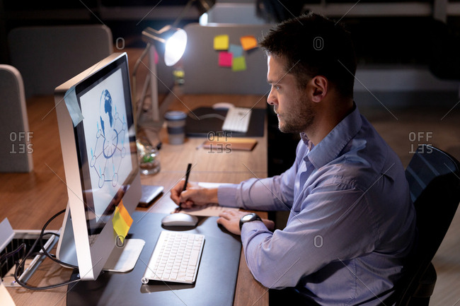 Side view of a young Caucasian professional man working late in a modern office, sitting at a desk using a desktop computer, staring at the monitor and making notes