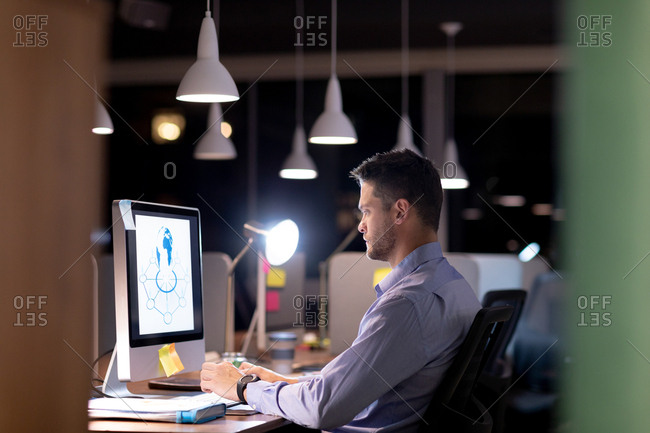 Side view of a young Caucasian professional man working late in a modern office, sitting at a desk using a desktop computer and staring at the monitor