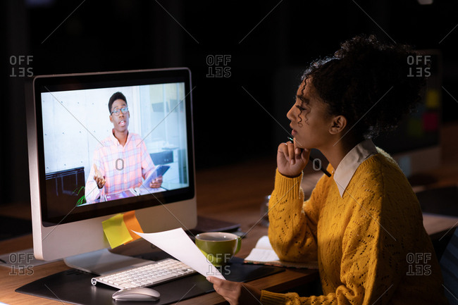 Side view of a young mixed race professional woman working late in a modern office, sitting at a desk in an on line meeting with a young African American man seen on her computer monitor