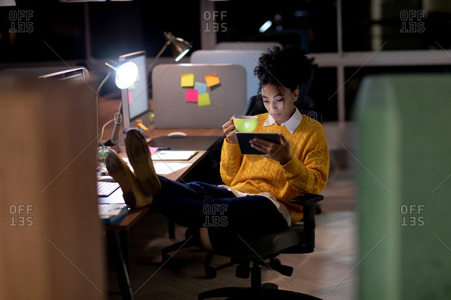 Front view of a young Caucasian professional mixed race woman working late in a modern office, sitting at a desk with her feet up using a tablet computer and holding a cup