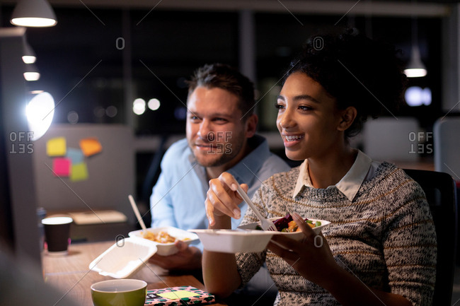 Front view of a young Caucasian professional man and mixed race woman working late in a modern office, sitting at a desk eating takeaway food and looking at a computer monitor together smiling