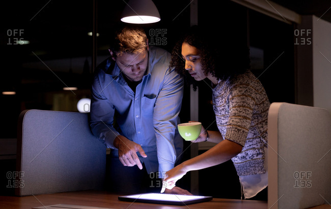 Front view of a young Caucasian professional man and mixed race woman working late in a modern office standing at a desk, looking at a tablet computer together, the woman touching the screen and holding a cup