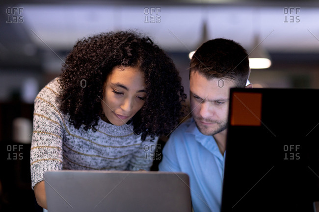 Front view close up of a young Caucasian professional man and mixed race woman working late in a modern office at a desk using a laptop computer together