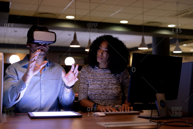 Front view of a young Caucasian professional man and mixed race woman working late in a modern office sitting at a desk, the woman using a computer and the man wearing a VR headset with his hands raised, a tablet computer with a lit screen on the desk in front of him