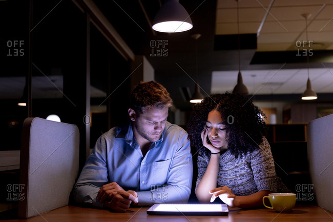 Front view of a young Caucasian professional man and mixed race woman working late in a modern office sitting at a desk, looking at a tablet computer together