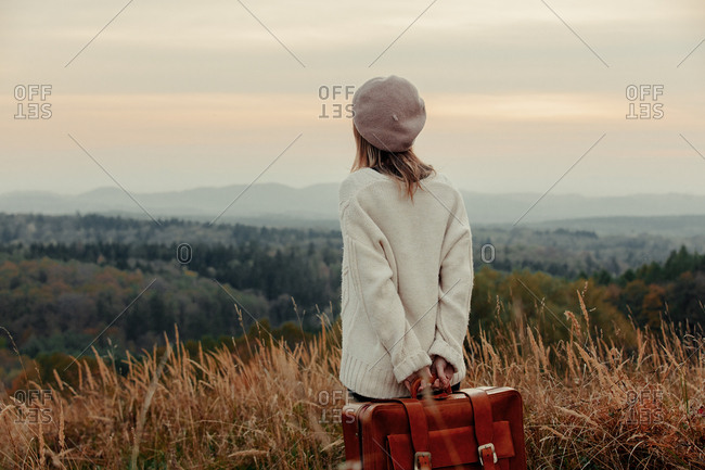 Style girl with suitcase at countryside with mountains on background