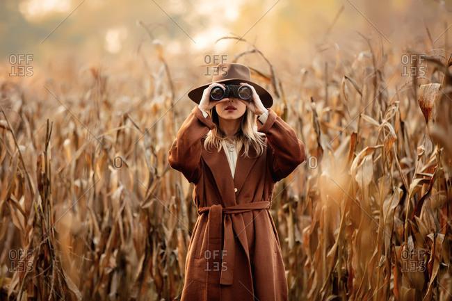Style woman with binoculars on corn field in autumn time season