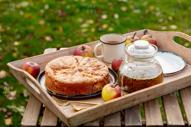 Apple pie and tea on tray on table in a garden