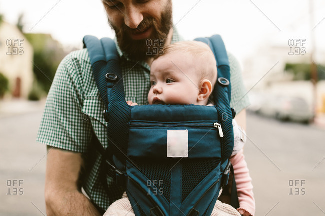 Baby girl being carried by her father in a carrier