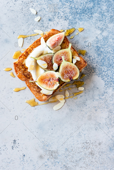 French toast with yogurt, fresh figs, almonds and honey, top view