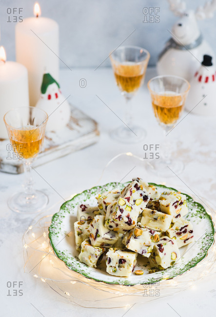 Homemade white chocolate fudge with cranberries and pistachio nuts on plate over light background, candles and festive decorations