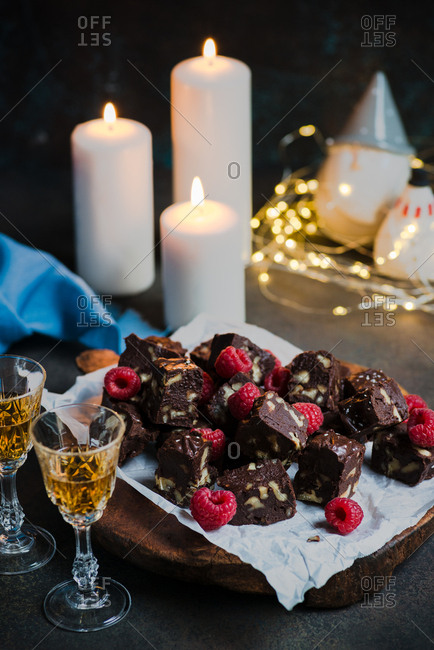 Homemade dark chocolate fudge with fruits and nuts on wooden board over dark background, candles and festive decorations