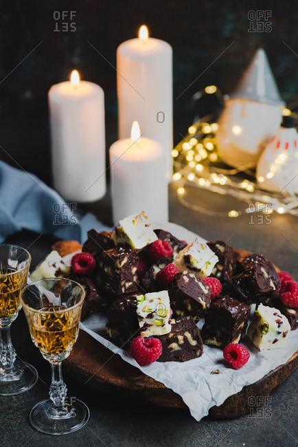 Homemade white and dark chocolate fudge with fruits and nuts on wooden board over dark background, candles and festive decorations
