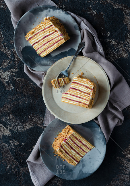 Slices of layered honey cake on plates over dark backdrop Russian Medovik cake top view