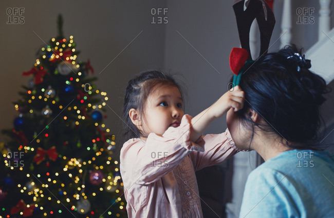 Daugher putting on reindeer antlers to her mother