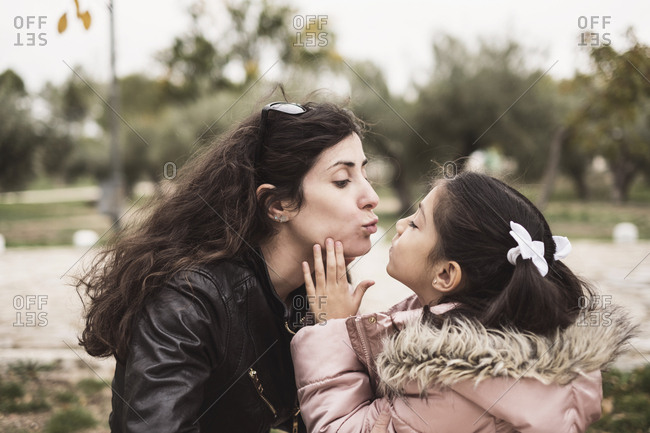 little girl kissing her mother in outdoors winter day in park.