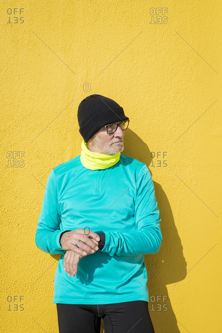 Senior man checking his wristwatch after exercising standing against a yellow wall