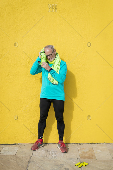 Senior jogger standing against a yellow wall while using a towel after exercising