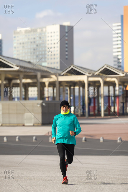 Front view of a senior man jogging outdoors in the city