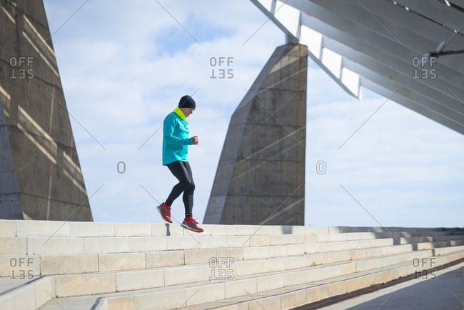 Side view of senior man jogging upstairs in the morning