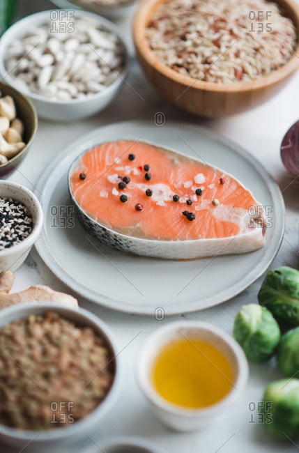 Raw salmon steak on ceramic plate ready for cooking with green vegetables, rice, beans and nuts on background