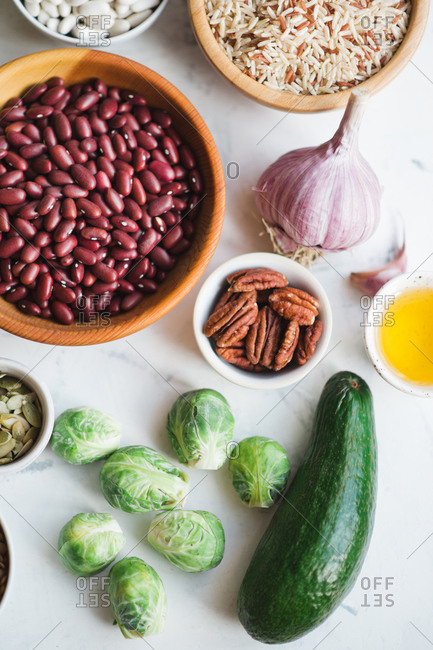Healthy food set:  beans, green vegetables, rice, oil and nuts on marble background copy space