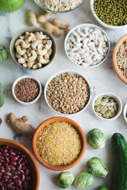 Healthy food set: beans, green vegetables, cereal, rice and nuts on marble background copy space
