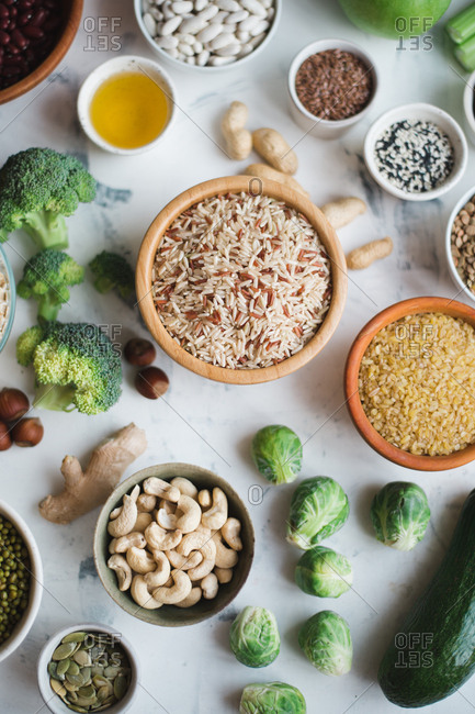 Healthy food set: rice, green vegetables, cereal, nuts and beans on marble background copy space