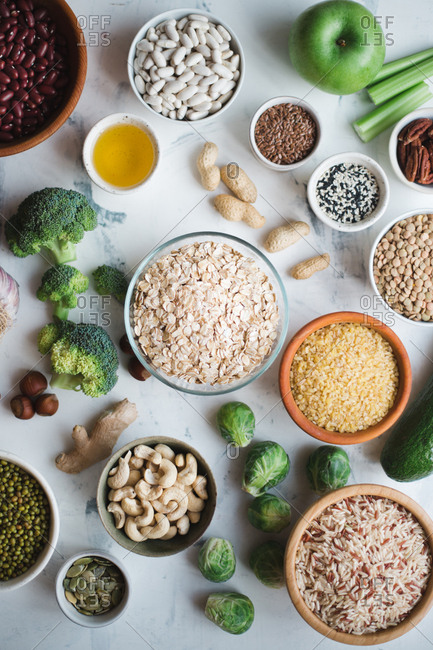 Healthy food set: oatmeal, green vegetables, lentil, rice, nuts and beans on marble background copy space