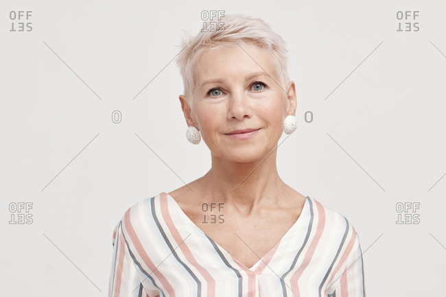 Elegant middle-aged woman smiling looking at camera horizontal chest up portrait