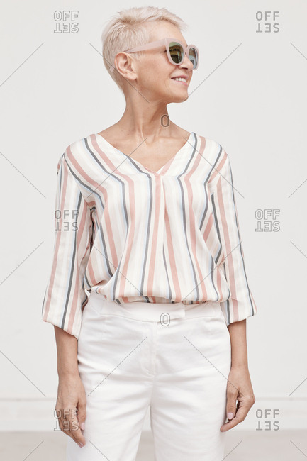 Medium long vertical portrait of stylish middle-aged woman standing against white background