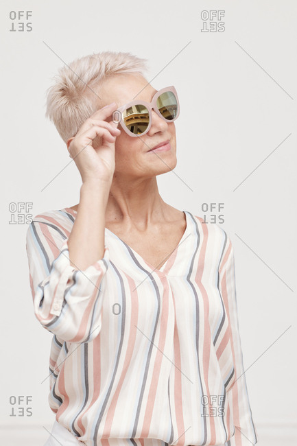 Medium portrait of mature woman wearing stylish striped blouse and sunglasses looking away
