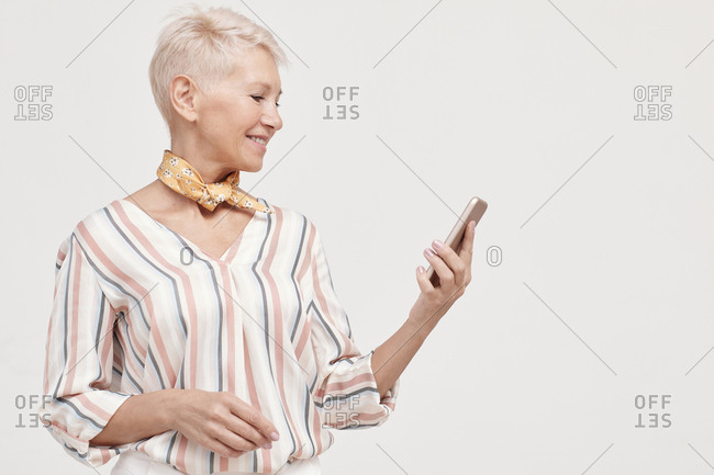 Middle-aged woman watching something on her smartphone horizontal portrait