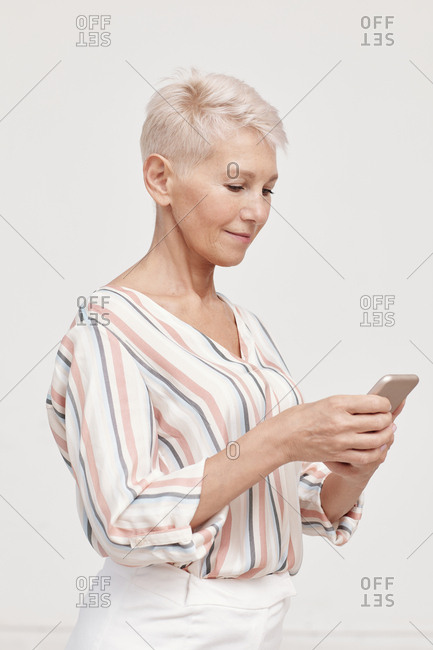 Mature woman wearing stylish spring outfit using smartphone vertical medium shot