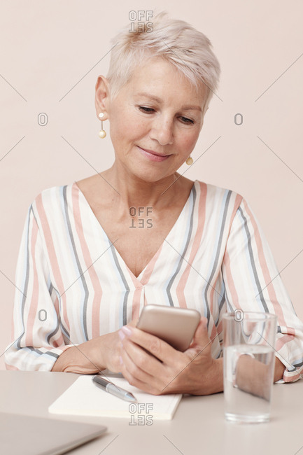 Modern mature businesswoman sitting at office table using her smartphone