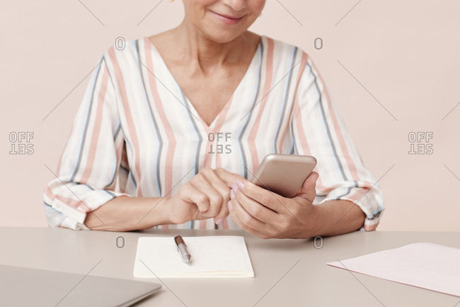 Horizontal shot of mature woman sitting at office table texting something on her smartphone