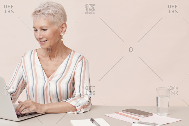 Horizontal shot of mature woman sitting at office table working on her laptop, copy space