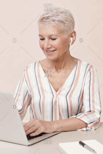 Stylish woman wearing modern wireless earphones working on her computer vertical shot