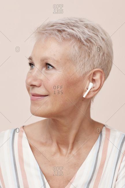 Modern mature woman wearing wireless earphones looking away vertical portrait