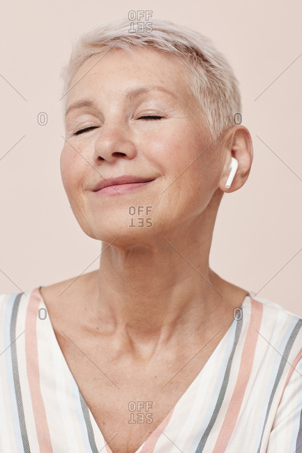 Mature woman wearing wireless earphones listening to music with eyes closed portrait